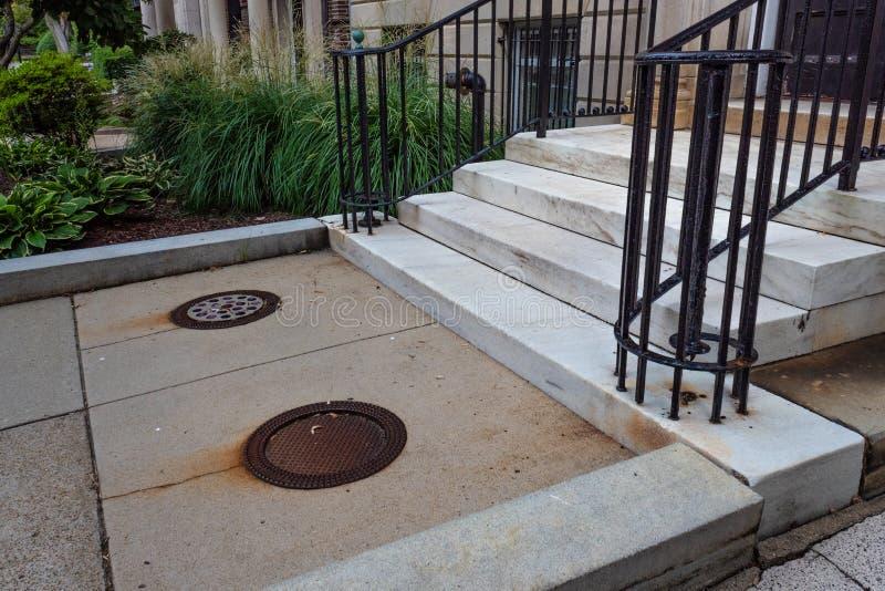 Wjazd z kamienia brązowego ze schodami marmurowymi i barierami żelaznymi, chodnik z pokrywami włazów, piękne zagospodarowanie ter zdjęcia royalty free