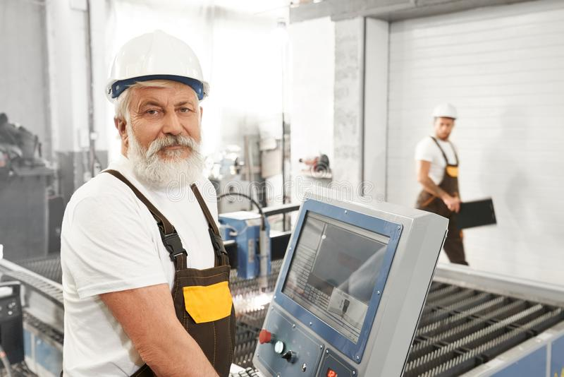 Wlder male worker of metal factory standing near computer. Front view of elder male worker of metal factory standing near computer, looking at camera and posing stock image
