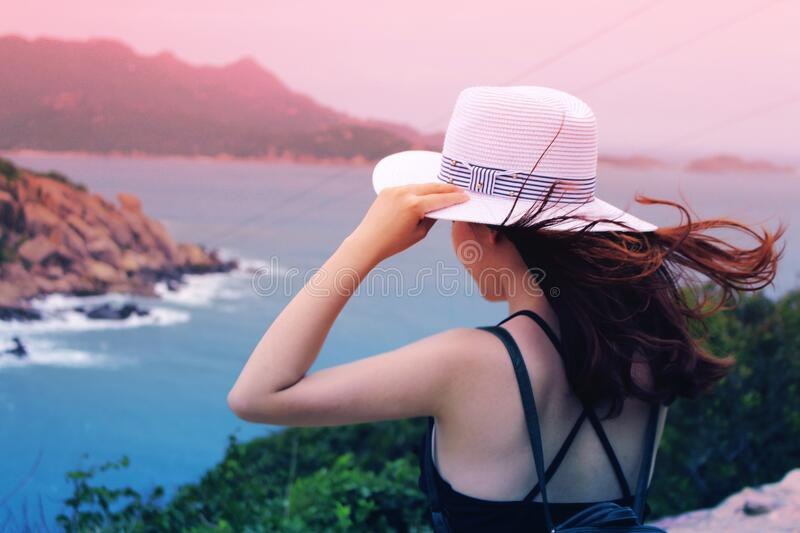 Wman Holding Wricker Shade Hat on Ocean View stock image