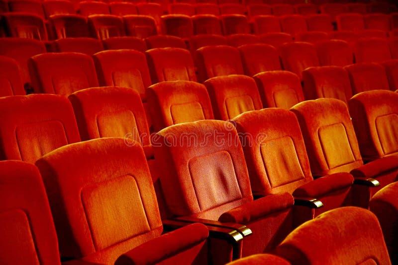 Wnętrza opróżniają czerwonawych kinowych krzeseł siedzenia w skromnym indoors obraz royalty free