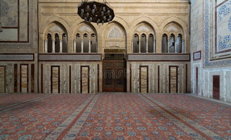 Wnętrze Al Rifaii Meczetowy Królewski meczet z dużym żelaznym świecznikiem, dekorującą marmur ścianą i ozdobnym drewnianym drzwi, obrazy royalty free