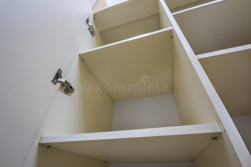 Wnętrze biała plastikowa gabineta lub odzieży garderoba z wiele pustymi półkami z otwarte drzwimi Meblarski projekt i instalacja obraz royalty free