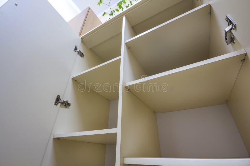 Wnętrze biała plastikowa gabineta lub odzieży garderoba z wiele pustymi półkami z otwarte drzwimi Meblarski projekt i instalacja zdjęcie royalty free
