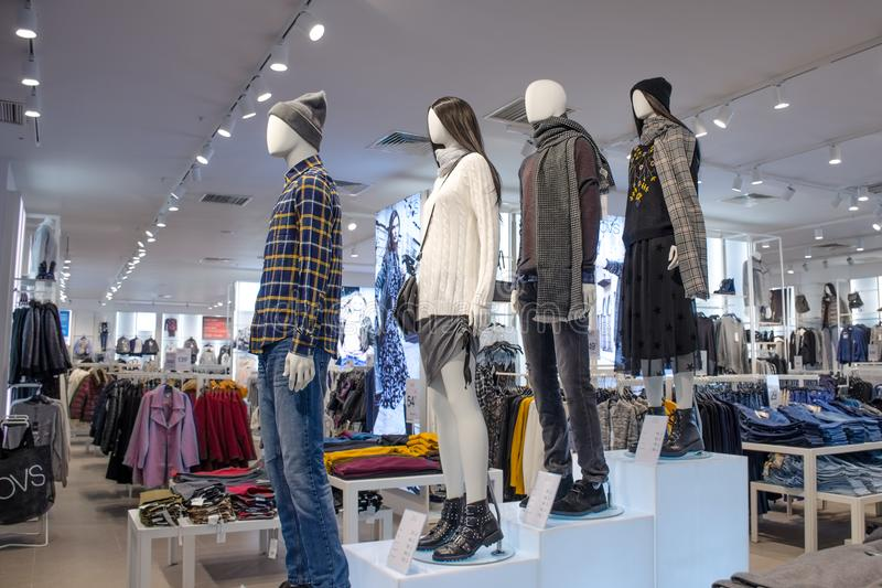 Wnętrze które stojakami na różnych poziomach są mannequins w formie mężczyzna i kobieta sklep odzieżowy zdjęcie royalty free