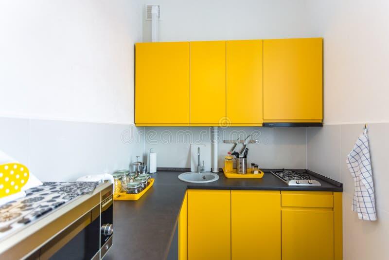 Wnętrze nowożytna kuchnia w loft płaskim mieszkaniu w minimalistic stylu z żółtym kolorem zdjęcie stock