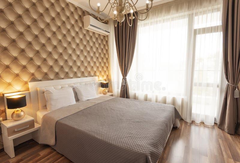 Wnętrze nowożytna sypialnia z wygodnym dwoistym łóżkiem Windows z długimi zasłonami, draperią i sheers, Wewnętrzna fotografia obrazy stock