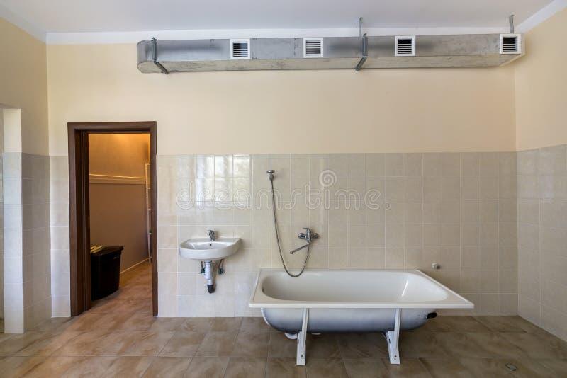 Wnętrze przestronna lekka łazienka z białą wanną, zlew, kafelkowa podłoga, ściany, i i obrazy stock