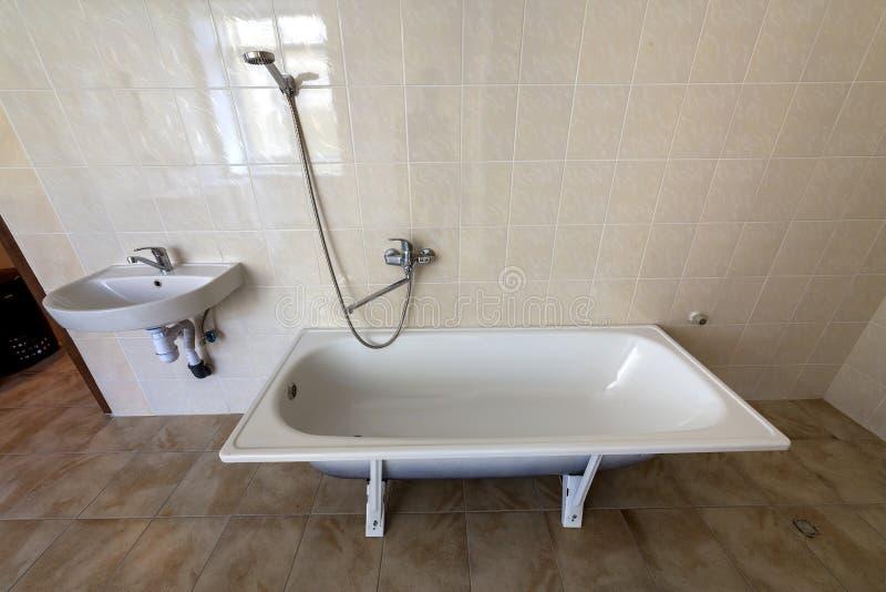Wnętrze przestronna lekka łazienka z białą wanną, zlew, kafelkowa podłoga, ściany, i i fotografia stock