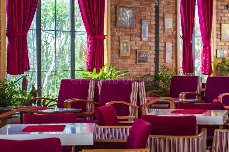 Wnętrze wygodna miastowa kawiarnia z miękkimi wygodnymi krzesłami w czerwonych kolorach z ścianami z cegieł obraz stock