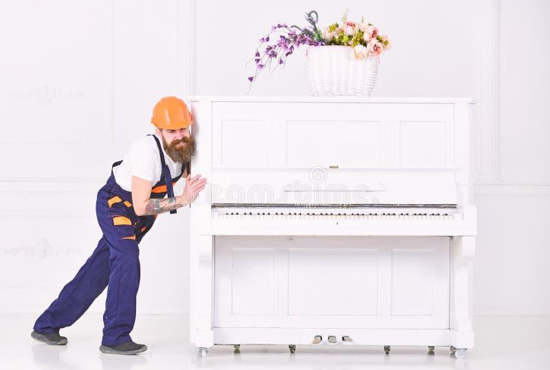Wnioskodawca marszczy brwi podczas gdy ruszający się ciężkiego pianino Zmęczony facet przenosi materiał w mieszkaniu odizolowywaj obrazy royalty free