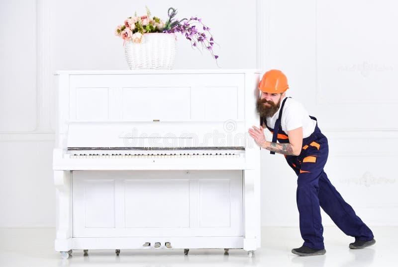 Wnioskodawca marszczy brwi podczas gdy ruszający się ciężkiego pianino Zmęczony facet przenosi materiał w mieszkaniu na białym tl fotografia stock