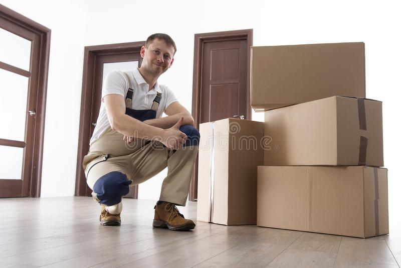 Wnioskodawca z kartonami w mieszkaniu Przeniesienie usługa Ładowacz trzyma kciuk up zdjęcie royalty free