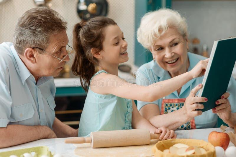 Wnuczka i dziadkowie gotuje wpólnie fotografia royalty free