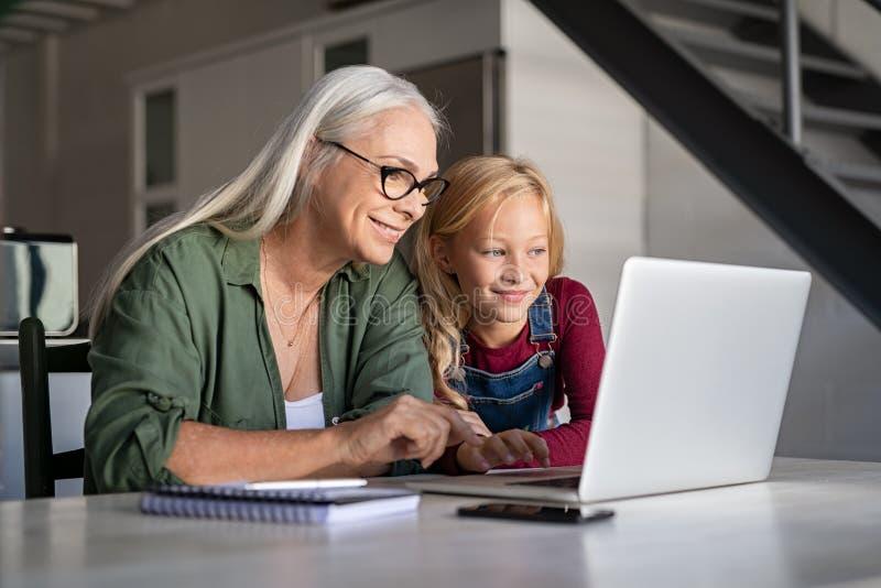 Wnuczki i seniora kobieta używa laptop obraz royalty free