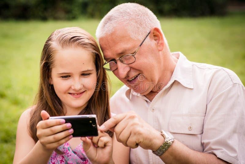 Wnuk pokazuje dziadek smartphone fotografia stock