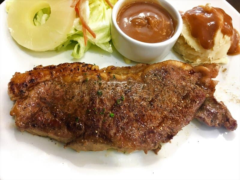 Wołowina stek Piec na grillu stek z pikantność, dłoniaki i warzywa na białym talerzu zdjęcie stock