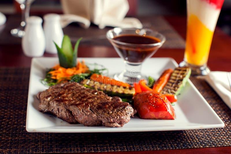 Wołowina stek z piec na grillu warzywami słuzyć na bielu talerzu szef kuchni poj?cia karmowa ?wie?a kuchni oleju oliwka nad dolew zdjęcie stock