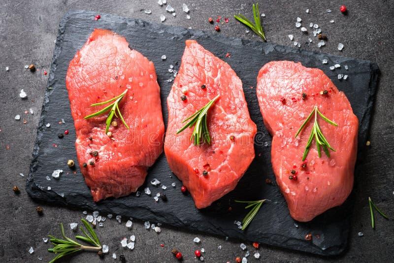 Wołowina stek z rozmarynami i pikantność na czarnym tle fotografia stock