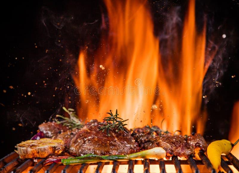 Wołowina stki na grillu z płomieniami obrazy royalty free