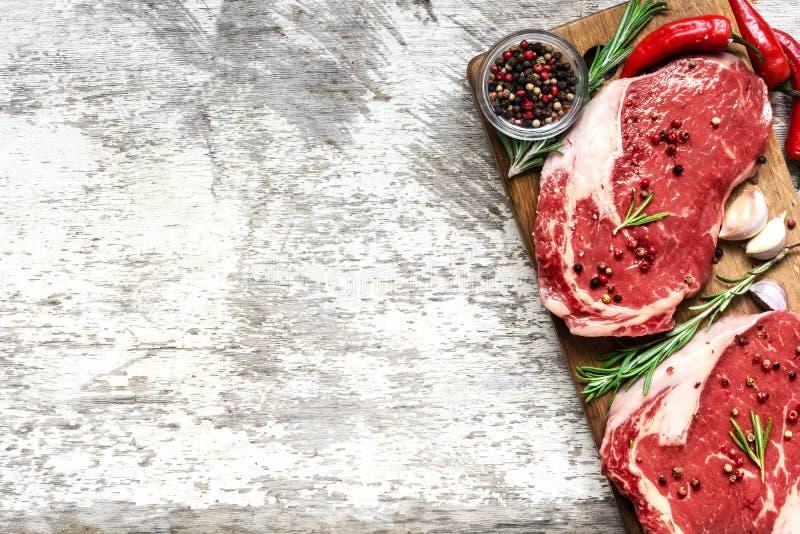 Wołowina stku surowy mięso z pikantność, chili pieprzem i rozmarynami na drewnianej desce nad nieociosanym drewnianym tłem, Odgór obrazy stock
