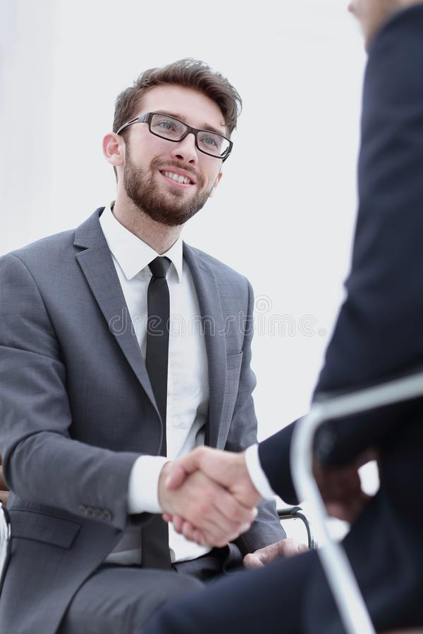 Wo focused coworkers sitting together in a modern office. Image of two young businessmen interacting at meeting in office royalty free stock photos
