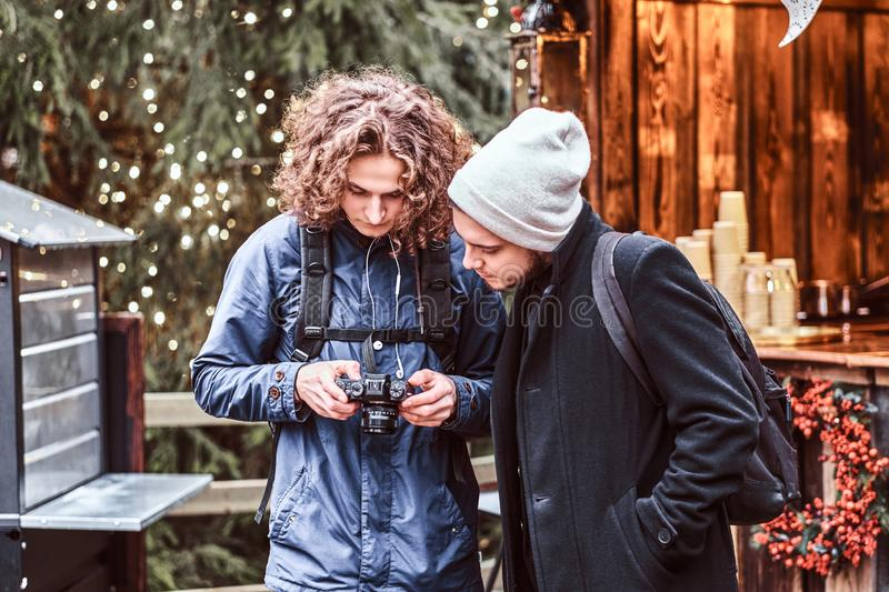 Wo handsome tourists with a camera stand and look for a photo. Two handsome tourists with a camera stand and look for a photo walking around the decorated market royalty free stock image