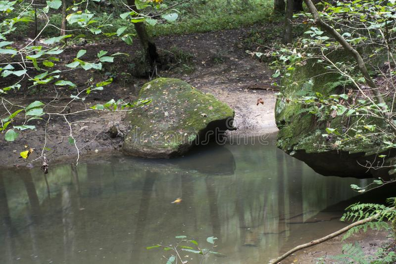 Wo Large boulders next to stream. Two large moss covered boulders next to a slow moving creek in Hocking Hills State Forest at the Old Man`s Cave area near Logan royalty free stock photos