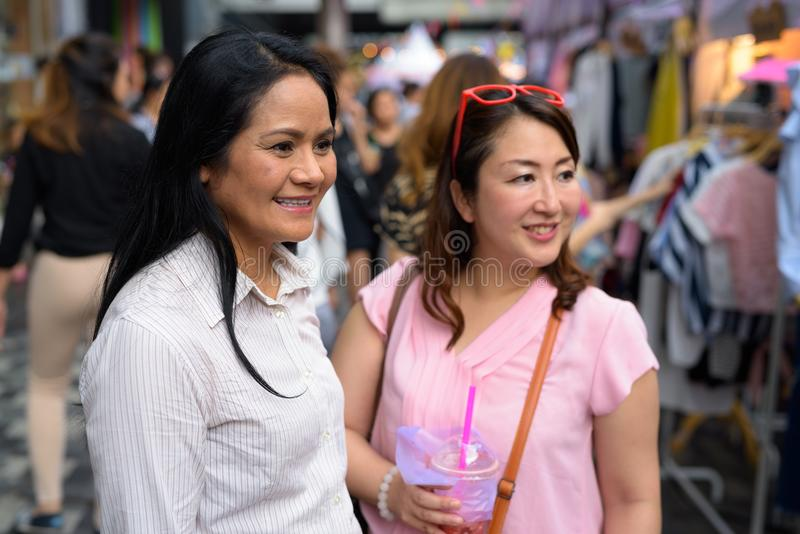 Wo mature Asian women shopping together in the street market. Portrait of two mature Asian women shopping together in the street market of Bangkok, Thailand royalty free stock photos