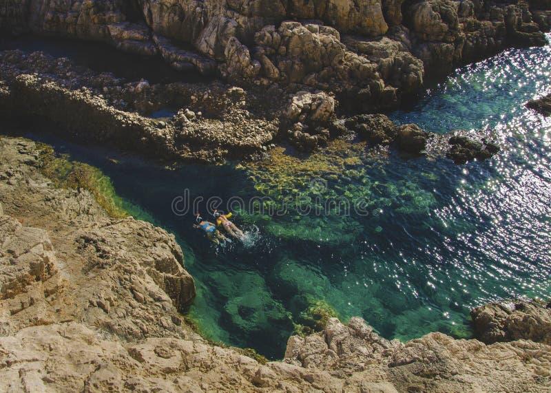 Wo-personer som simmar och snorklar i det kristallklara turkosvattnet i Korakonissi, Zakynthos arkivbilder