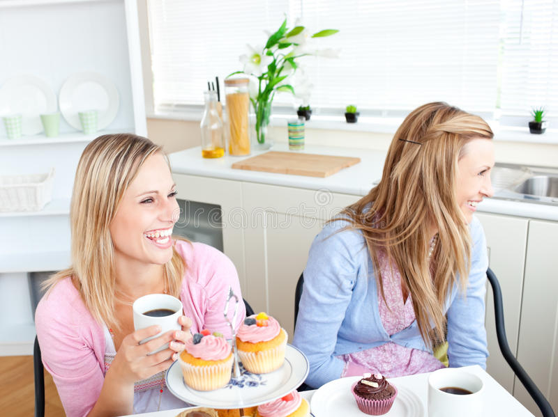 Wo women having the giggles. While eating pastries and drinking coffee in the kitchen royalty free stock image