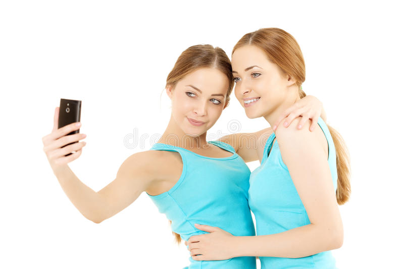 Wo women make the photo to mobile phone. Two smiling women make the photo to mobile phone royalty free stock photography