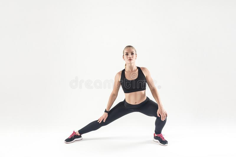 Woaman doing stretching and looking at camera. Athletic, fitness concept. Studio shot, gray background stock photo