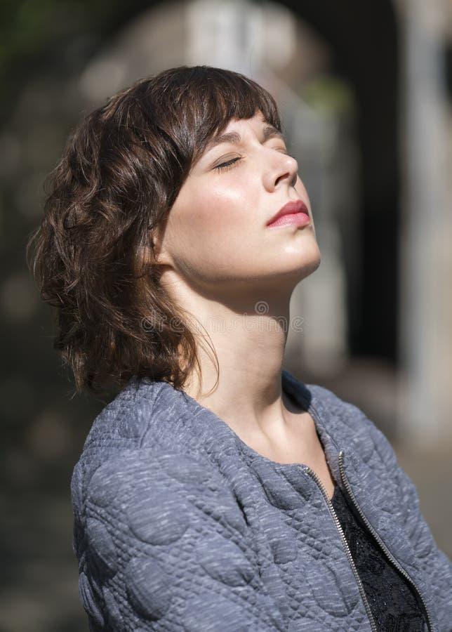 Woaman enjoying warm sunlight. Beautiful young woman with eyes closed enjoying the sunlight outdoors stock photography