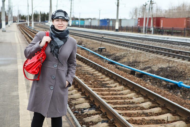 Woaman waiting on railway station. Portrait of fashion young Caucasian woman standing on railway station. Looking far away. Copy space stock photo