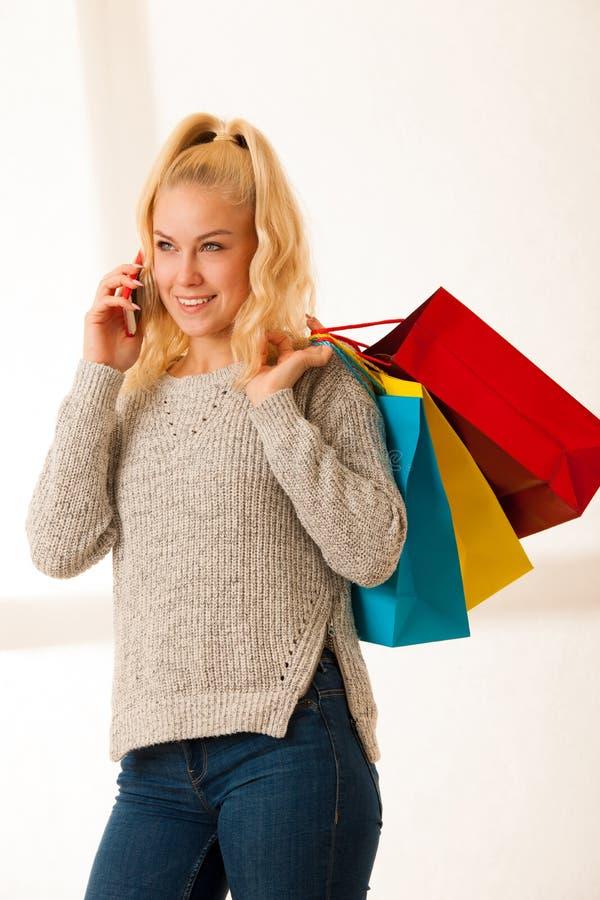 Woamn говорит на телефоне после ходить по магазинам стоковое фото