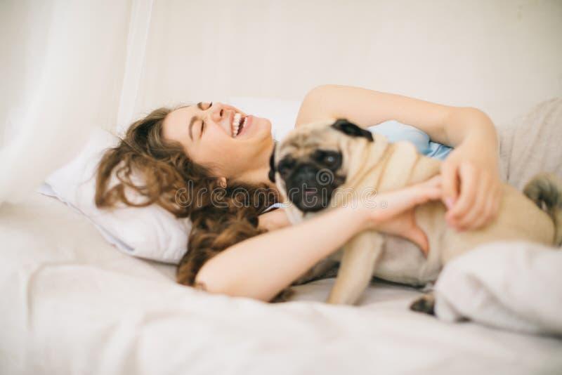 Woamn novo de riso que joga na cama com cão fotografia de stock