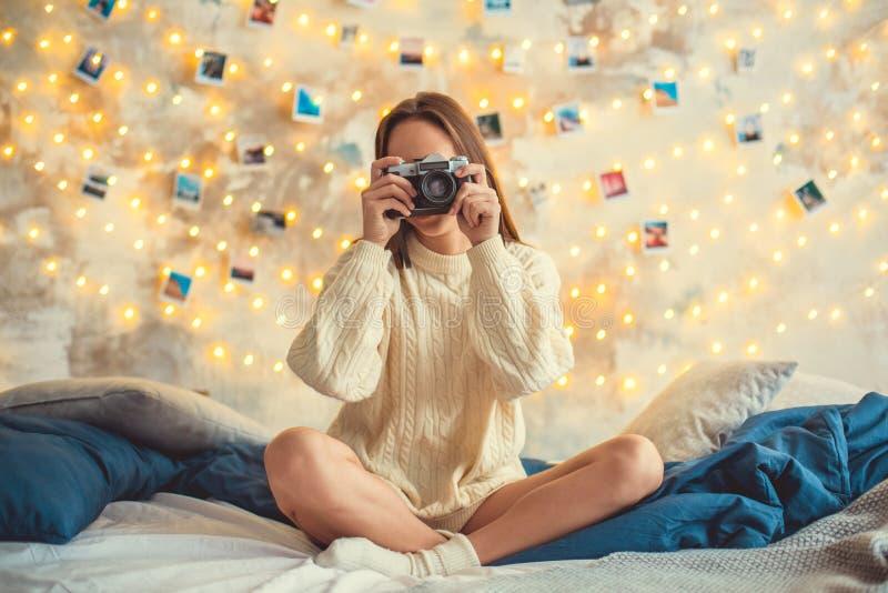 Wochenende der jungen Frau verzierte zu Hause das Schlafzimmer, das Fotos machend sitzt stockfotografie