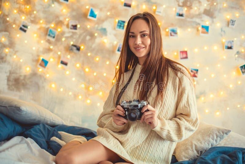 Wochenende der jungen Frau verzierte zu Hause das Schlafzimmer, das mit Kamera sitzt lizenzfreie stockfotos