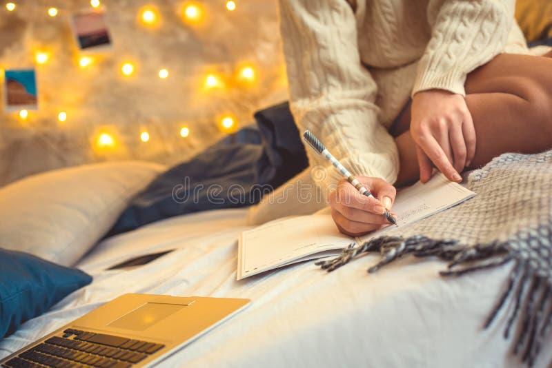 Wochenende der jungen Frau verzierte zu Hause sitzendes Schreiben des Schlafzimmers im Organisator stockfotos