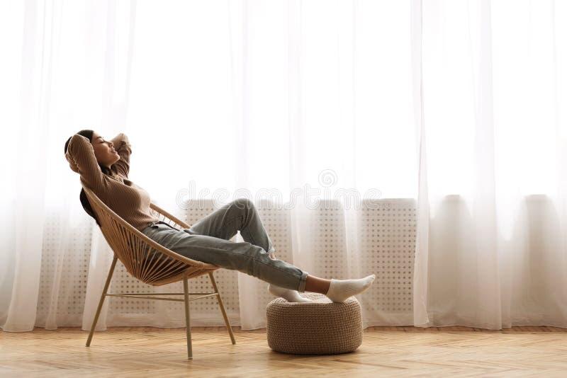 Wochenenden schließlich! Entspanntes Mädchen, das auf modernem Stuhl sitzt stockbild