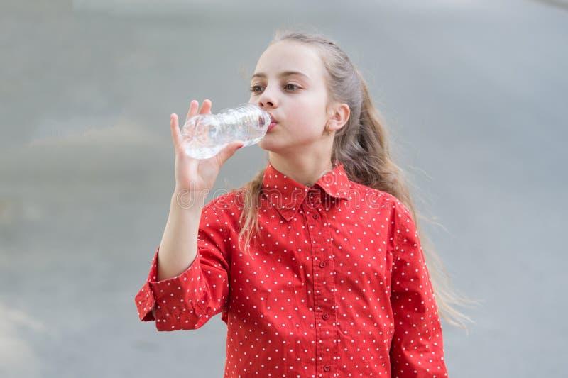 Woda jest ?yciem Spragniony dziecko pije świeżą wodę od plastikowej butelki Mała dziewczynka ma napój od bidonu obrazy stock