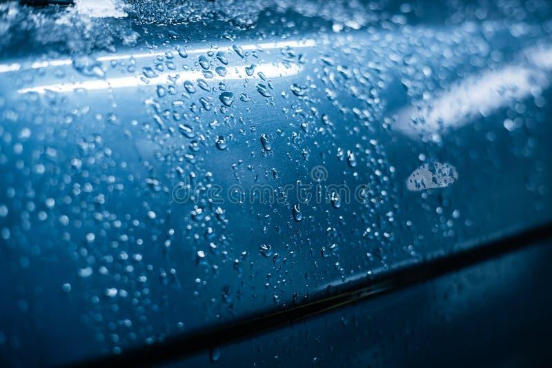 Woda opuszcza na powierzchni błękitny samochód zdjęcie royalty free