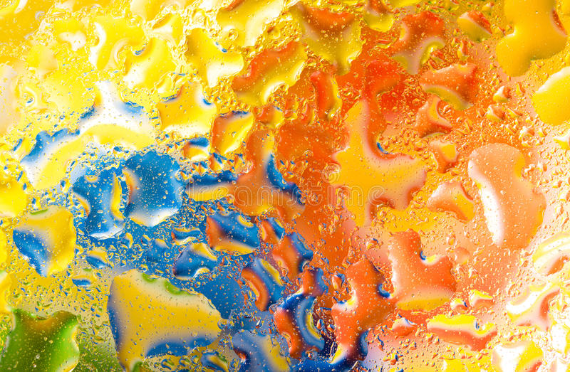 Woda opuszcza na szkle z zielonym błękitnym pomarańczowym tłem fotografia royalty free