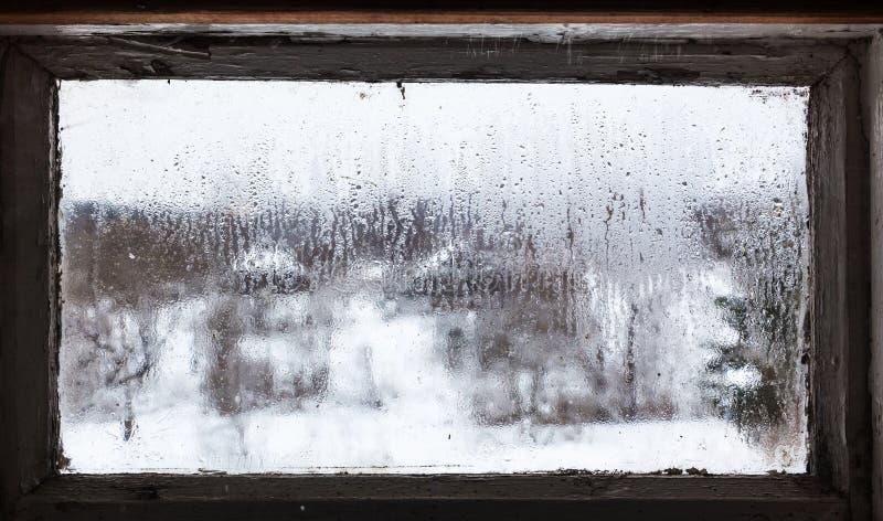 woda opuszcza od roztapiającego śniegu na zamarzniętym okno obraz royalty free