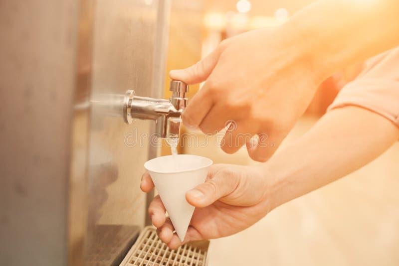 Woda pitna od wodnego pudełka nalewał w szklanego papieru rożek fotografia royalty free