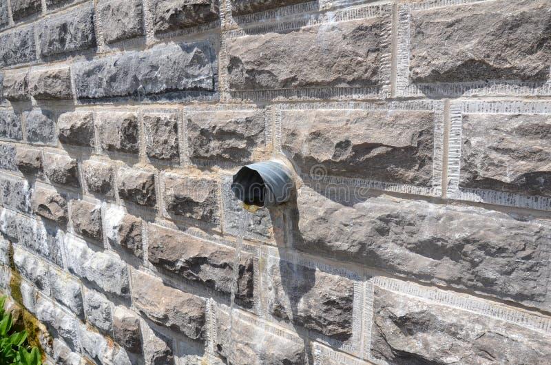 Woda wypływająca z rury w murze z cegły szarej zdjęcia royalty free