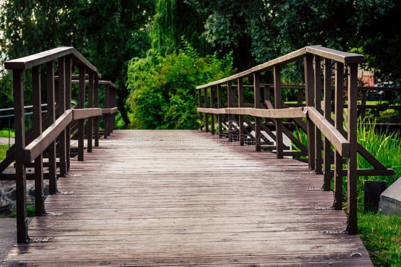 Wodden桥梁的喜怒无常的照片在一个公园,在成为不饱和的森林之间-,葡萄酒神色 库存图片