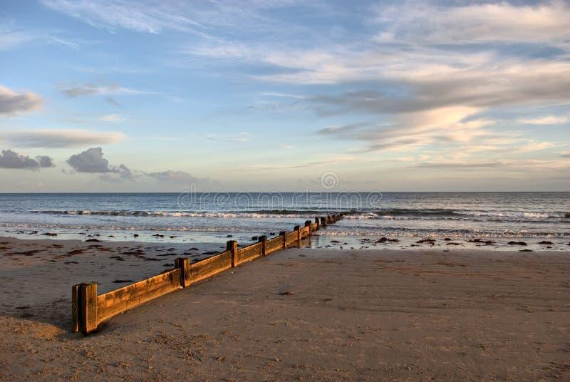 Wodden Wellenunterbrecher auf dem drastischen Himmel des Strandesprits stockfoto