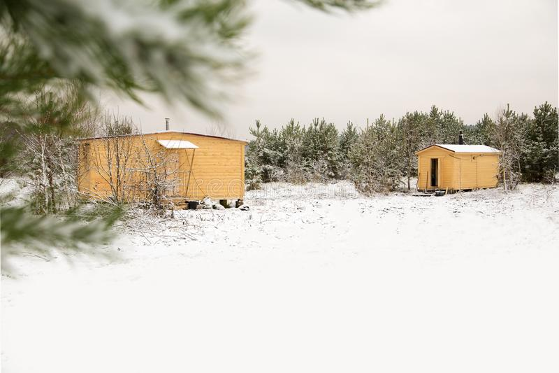 Woden kabin på fältet mot skog royaltyfri foto