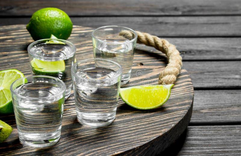 Wodka in einem Schnapsglas auf einem Behälter mit Scheiben des Kalkes lizenzfreie stockbilder